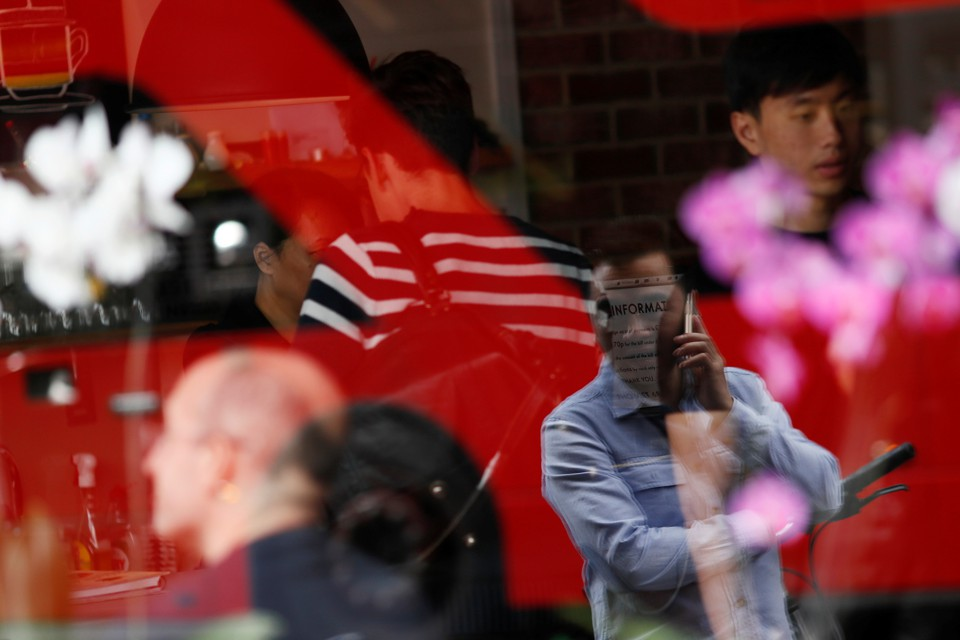 A man is reflected in a window as he uses his mobile phone