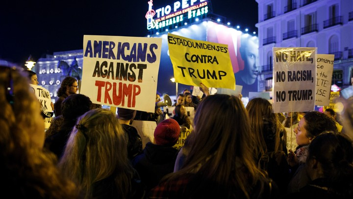 Demonstrators hold up signs during a protest against U.S. President-elect Donald Trump at the Puerta del Sol Square in central Madrid, Spain, December 2, 2016.