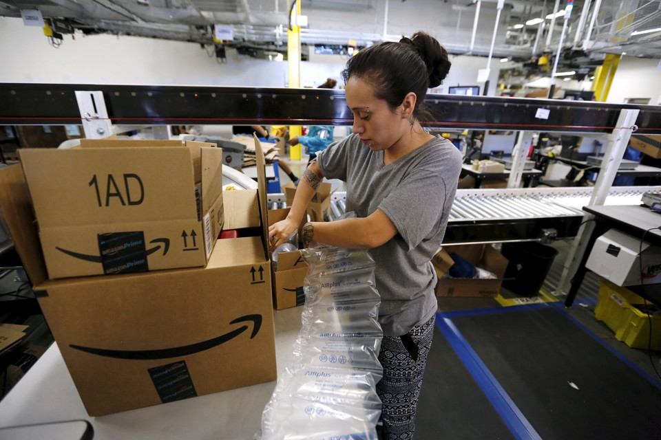 Monica Galvan secures customers' orders with air cushions at the Amazon Fulfillment Center in Tracy, California.