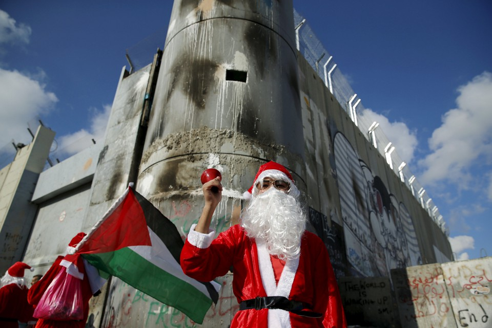 A Palestinian protester wearing Santa Claus costume stands in front of a section of the Israeli barrier during an anti-Israel protest in the city of Bethlehem on December 18, 2015.