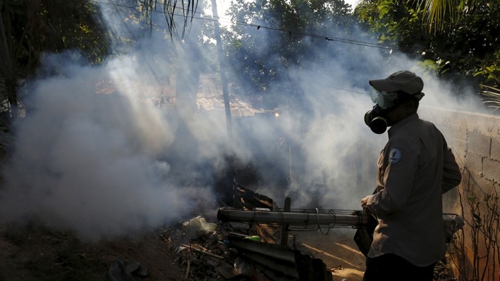 A health worker fumigates a neighborhood on the outskirts of Panama City
