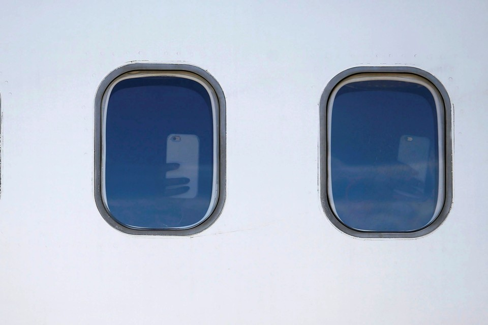 Two windows on the side of an airplane show hands holding up smartphones inside.