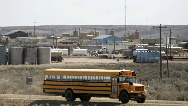 A yellow school bus drives down a dusty road with rolling plains in the background.
