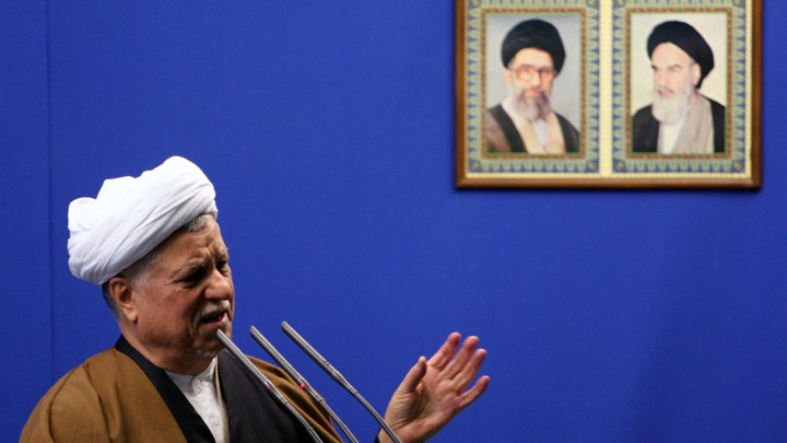 Former President Ali Akbar Hashemi Rafsanjani speaks under the pictures of Iranian late spritual leader Ayatollah Khomeini, right, and supreme leader, Ayatollah Ali Khamenei.