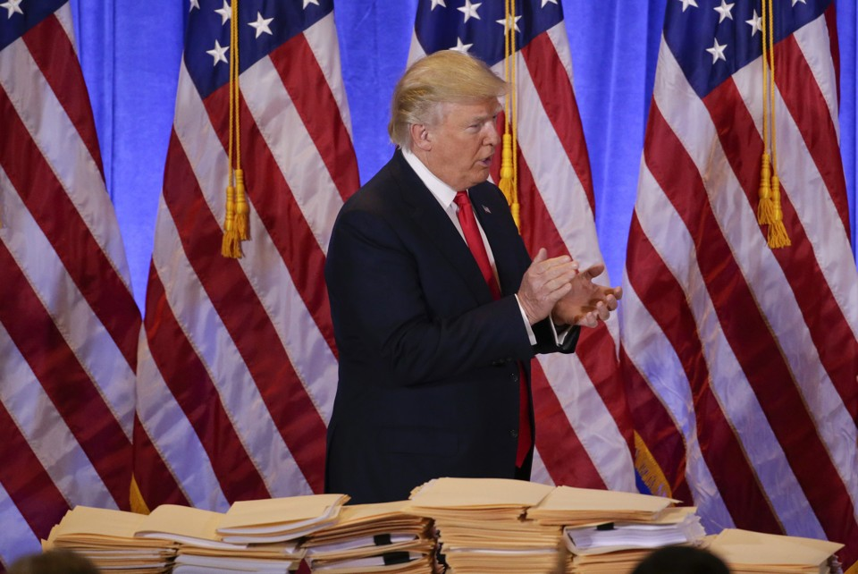 President-elect Donald Trump stands by a table covered with paperwork