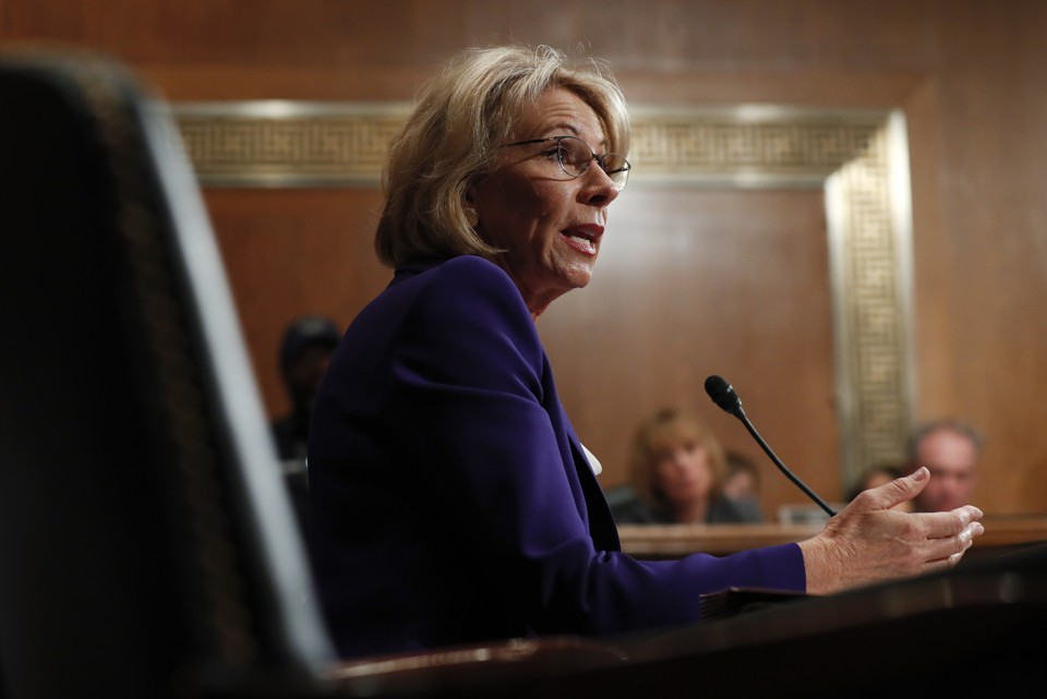 Betsy DeVos sits at a microphone during her hearing.