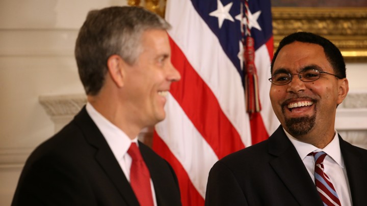 Arne Duncan and John King smile at one another