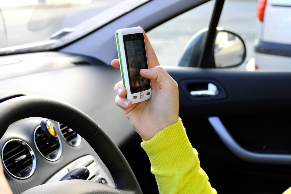 A driver uses a smartphone app in a car