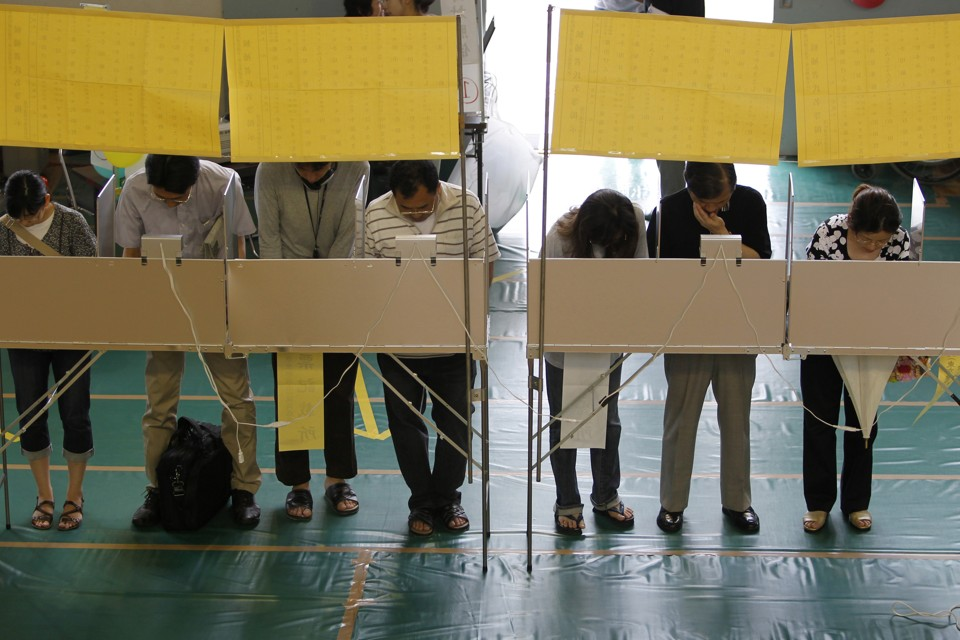 Voters fill out ballots for Japan's upper house election at a polling station in Tokyo on July 11, 2010.