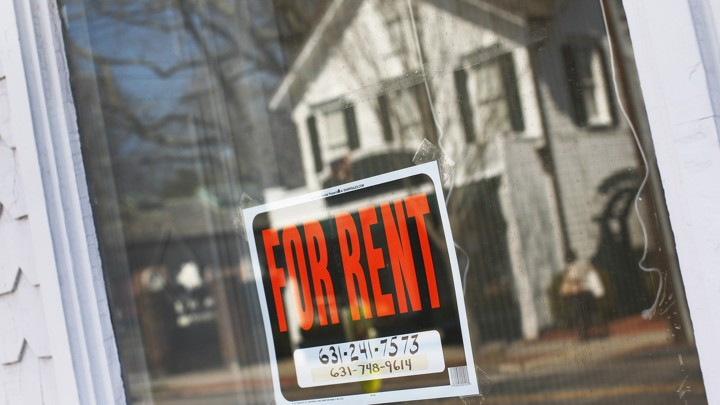 "A ""for rent"" sign hangs in the window of a home."