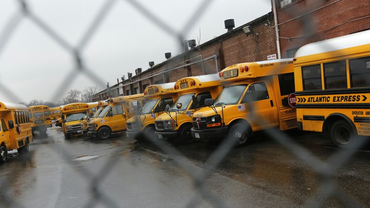 School buses photographed through a chain-link fence.