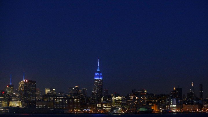 The New York skyline at night, with the Empire State Building lit up for World Autism Awareness Day