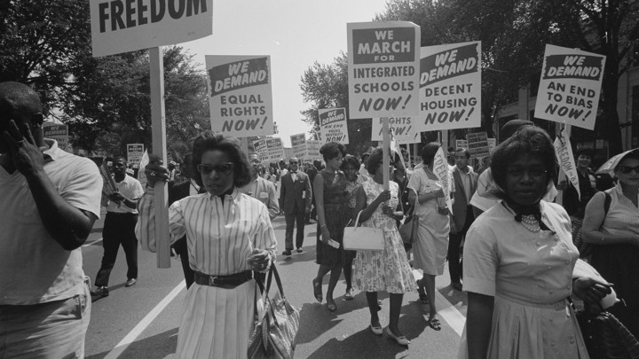 "A black and white photo featuring African Americans holding signs that read ""We demand equal rights now!"" ""We march for integrated schools now!"" and ""We demand decent housing now!"""