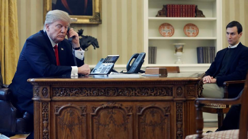 Donald Trump speaks on the phone as Jared Kushner looks on.