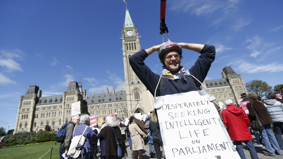 "Protester with telescope on head with sign saying, ""Desperately seeking intelligent light on Parliament Hill!"""