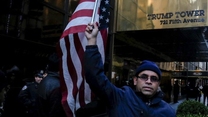 A Muslim man stands waving an American flag in front of the Trump Tower sign.