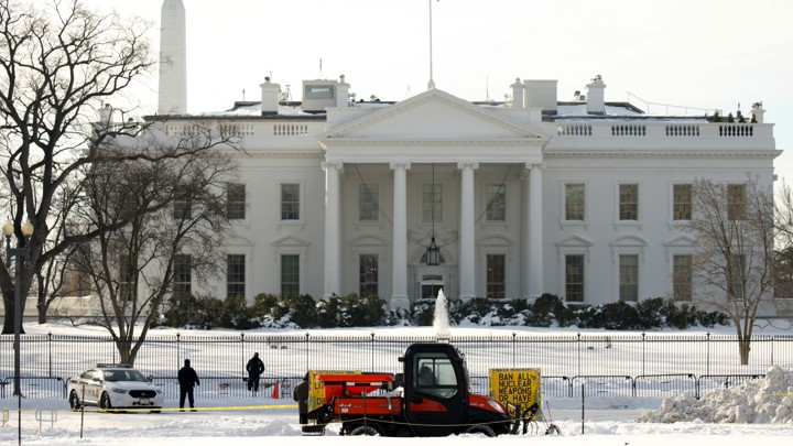 A worker drives a snow plow to clear the sidewalk in front of the White House in January of last year.