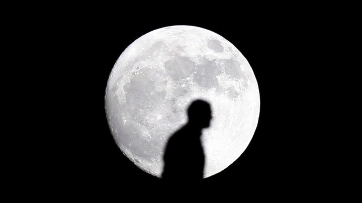 The silhouette of a man in front of the moon