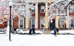 Students have a snowball fight in front of a large brick building with columns.