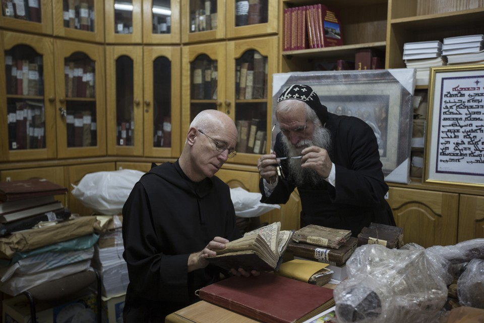 Father Columba Stewart inspects an ancient manuscript as a Syriac monk looks on at St. Mark's Syrian Orthodox Monastery in Jerusalem.