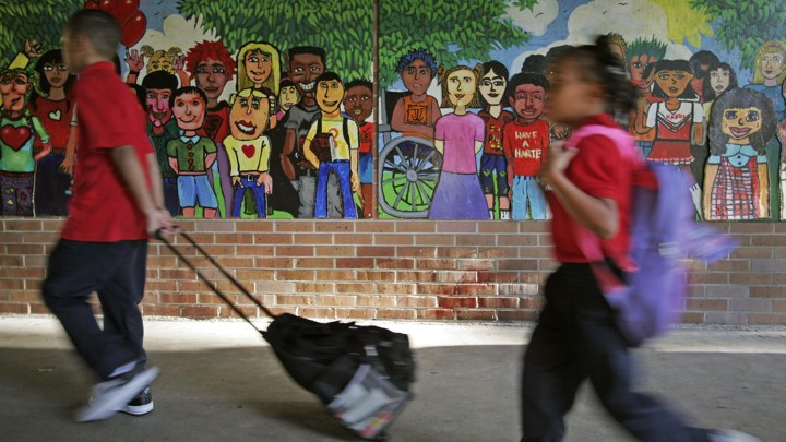 Two black children walk with backpacks past a mural depicting a diverse array of children.