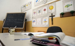 A teacher's desk is covered with papers in a classroom with a chalkboard and crucifix.