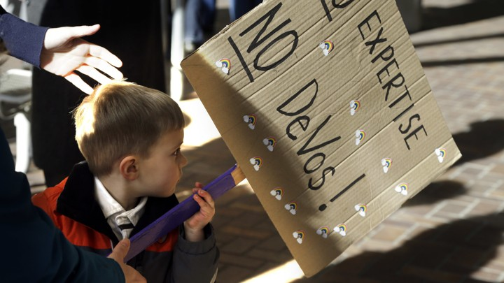 A 3-year-old boy carries a sign opposing Betsy DeVos`