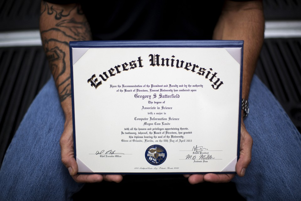 A man with tattoos on his arm holds a diploma.