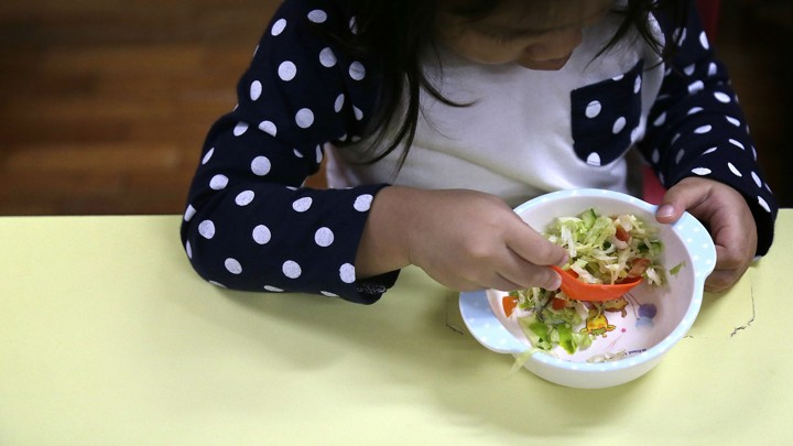 A child eats a bowl of salad.