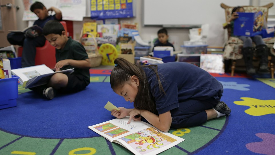 A girl crouches over a book on a colorful rug. Other children around her also have books on their laps.