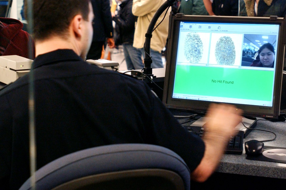A U.S. Customs and Border Protection agent checks an overseas visitor's fingerprints and image in a database.
