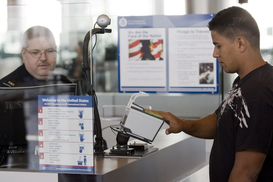 A traveler scans his fingerprints at the Houston airport as a customs officer monitors his computer.