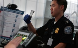 A traveler is fingerprinted while a border agent checks his paperwork.