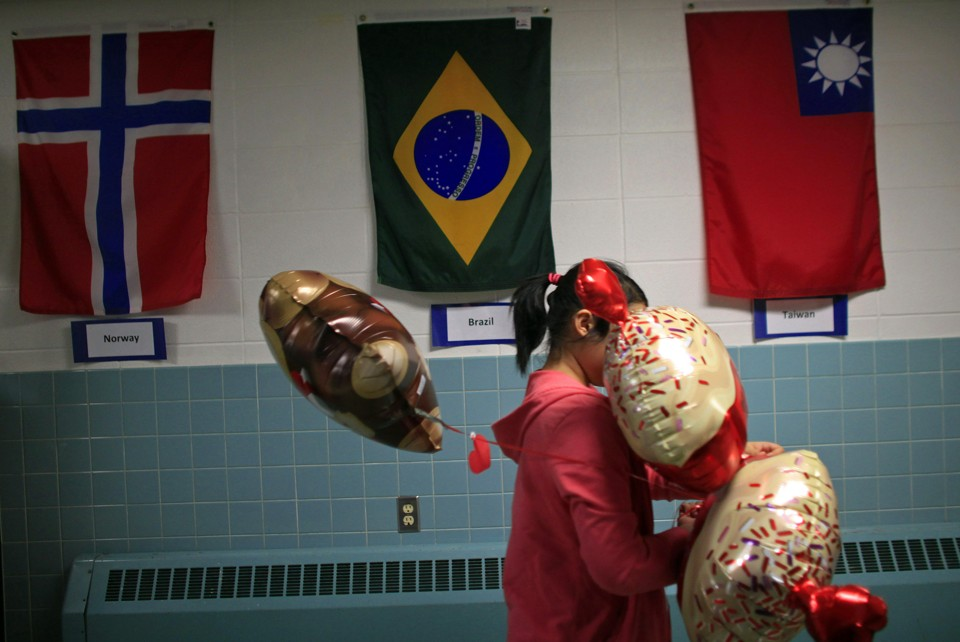 A student carrying balloons walks past the flags of Norway, Brazil, and Taiwan.