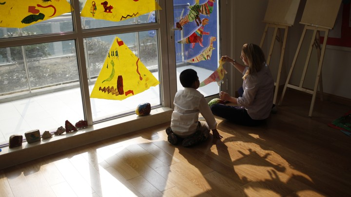 A child and adult sit together on the floor, playing with construction-paper dinosaurs.
