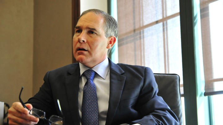 Scott Pruitt holds his glasses and looks out of the frame, with an upset expression on his face.