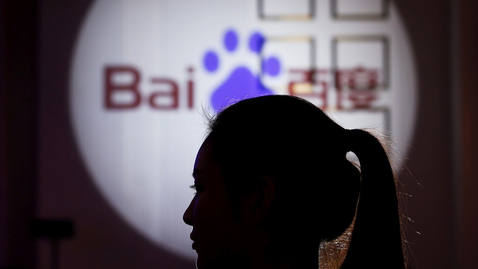 A woman is silhouetted against the Baidu logo