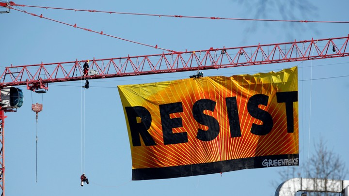 "A banner reading ""RESIST"" hangs off a crane near the White House in Washington, D.C."