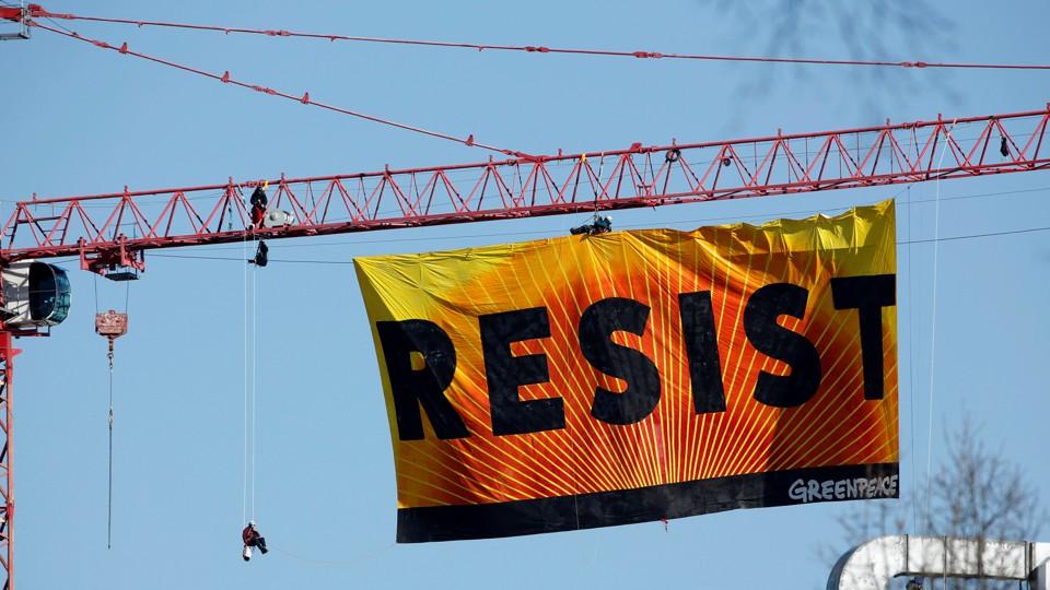 "A banner reading ""RESIST"" hangs off a crane near the White House in Washington, D.C."