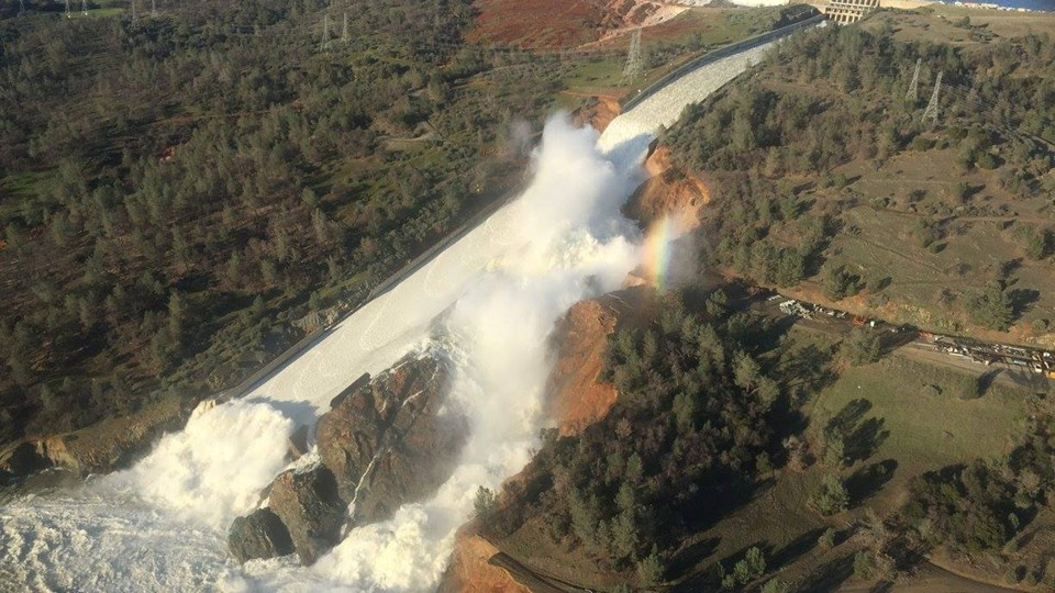 Water pours over the damaged main spillway at the Oroville Dam and over a hillside.