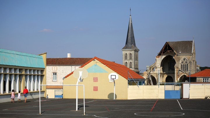 A playground is in the foreground. A church steeple is behind it.