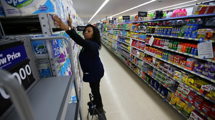 An employee places paper towels on a shelf at a store