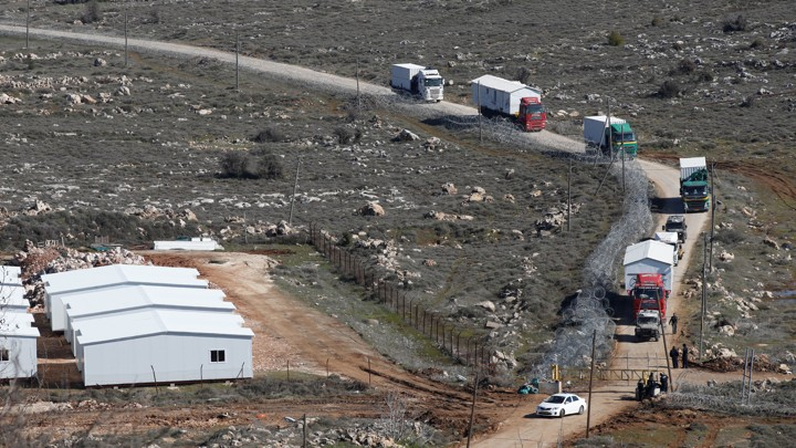 Trucks removing pre-fabricated homes drive along a road leading out of the recently evicted Israeli settler outpost of Amona.