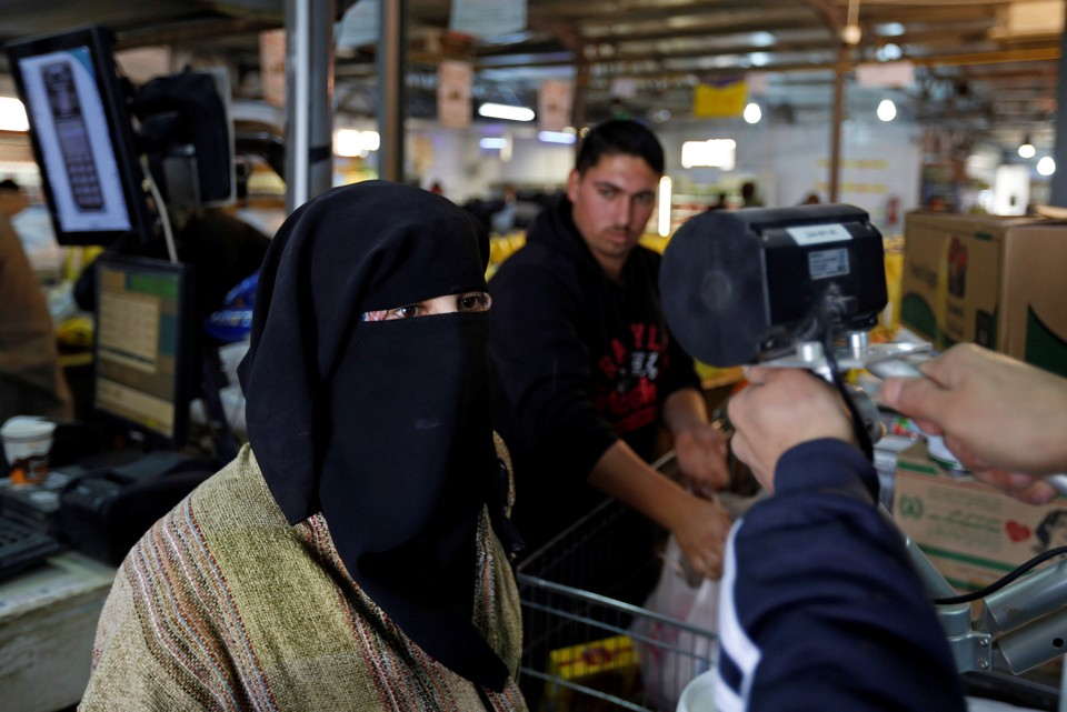 A Syrian refugee has her eyes scanned by a device to verify her identity so that she can receive her foodstuff at a refugee camp, in Mafraq, Jordan.