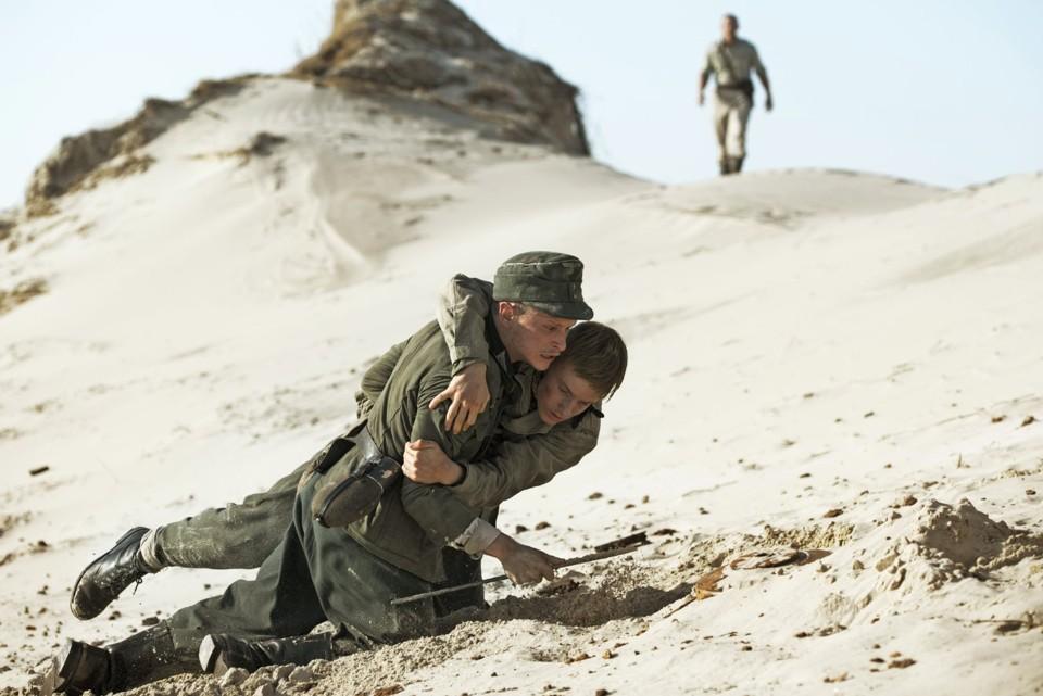 One German trooper, Anders, helps his fellow soldier, Hans, across the dunes in the Danish film, Land of Mine.