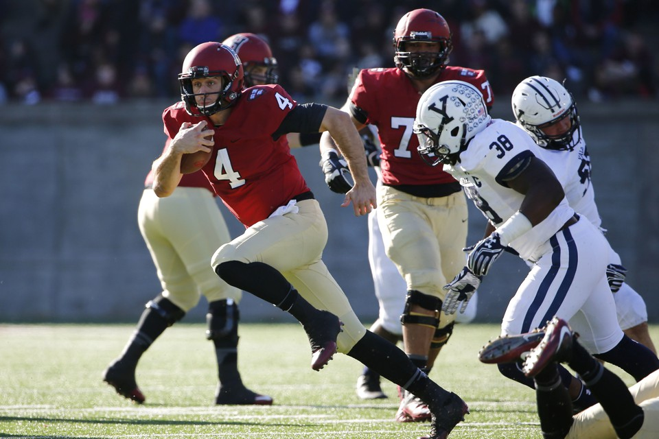 A Harvard player runs with the football away from the Yale defense