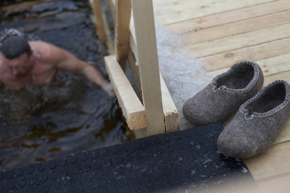 A Russian man eases himself into icy water while his slippers wait on a deck.