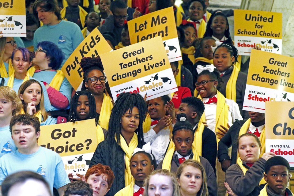 "People hold signs reading ""Let me learn,"" ""United for school choice,"" and ""Great teachers change lives."""