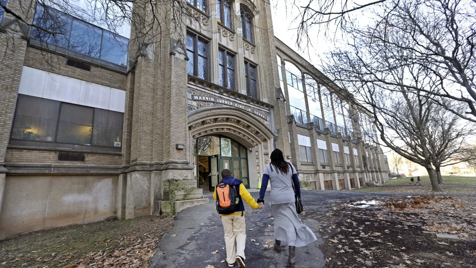 A mother and her son walk hand-in-hand into a brick school building. They are unrecognizable from the back.