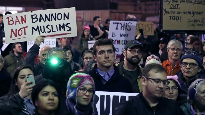 """People hold signs with phrases including """"Ban Bannon, not Muslims."""""""